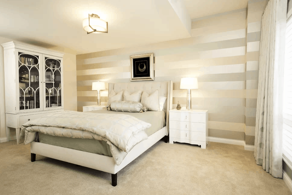 Eclectic primary bedroom boasting a classy wall and a lovely bed setup lighted by table lamps on both sides. The room also features carpeted flooring and glass windows.