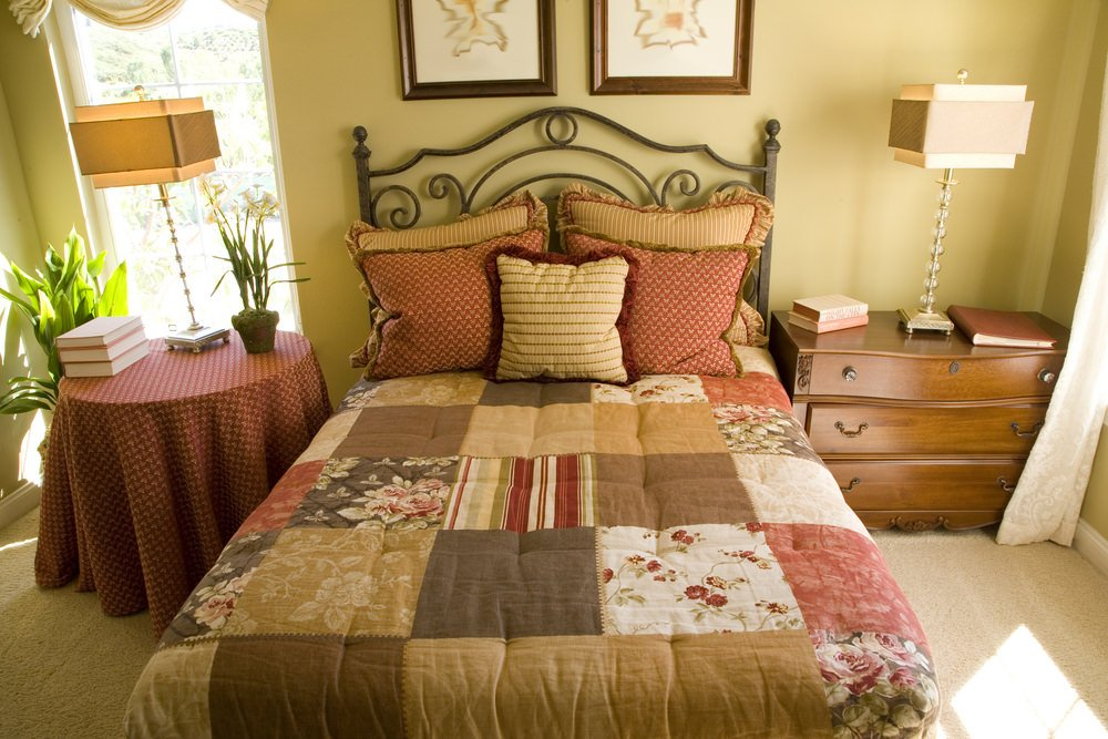 A close up look at this master bedroom's classy bed set lighted by stylish table lamps on both sides. The room is surrounded by brown walls.