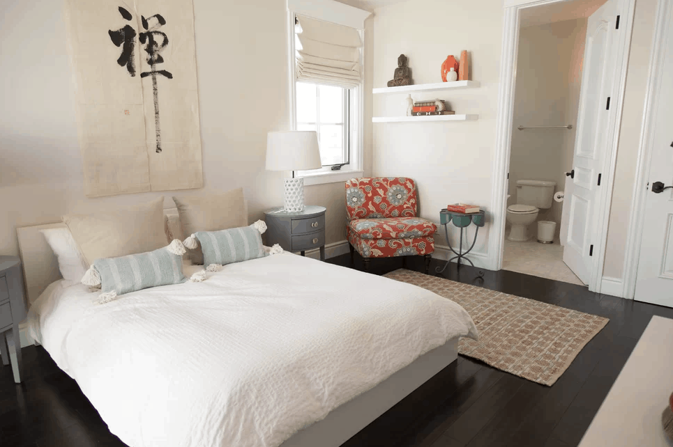 Primary bedroom featuring white walls and dark hardwood floors. It offers a comfy bed lighted by table lamps. The room has its own bathroom as well.