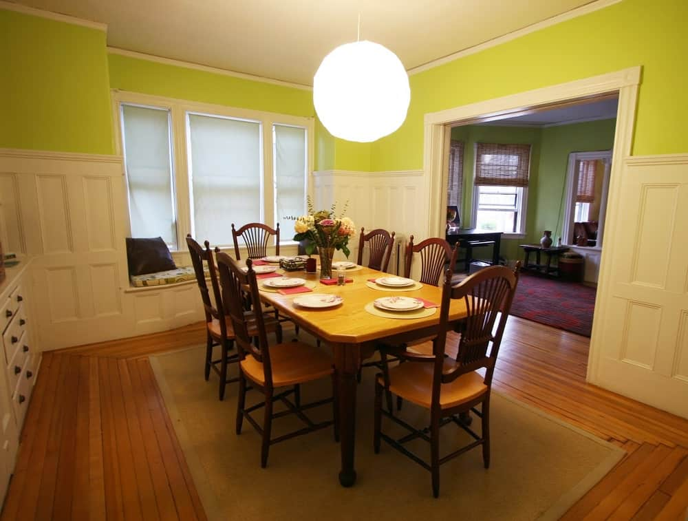 This bright dining room has lime green walls accented with white wood wainscoting illuminated by the brilliant spherical pendant light over the wooden table surrounded by slat-back wooden chairs.