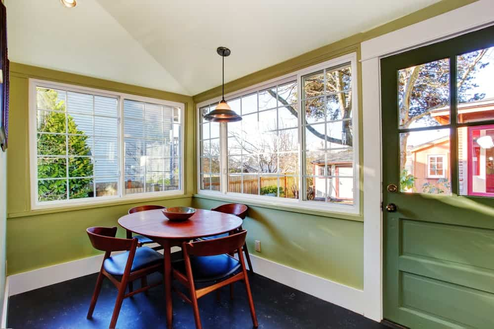 This is a small dining room with a round wooden table surrounded by wooden chairs against an alcove of green walls and wide French windows.