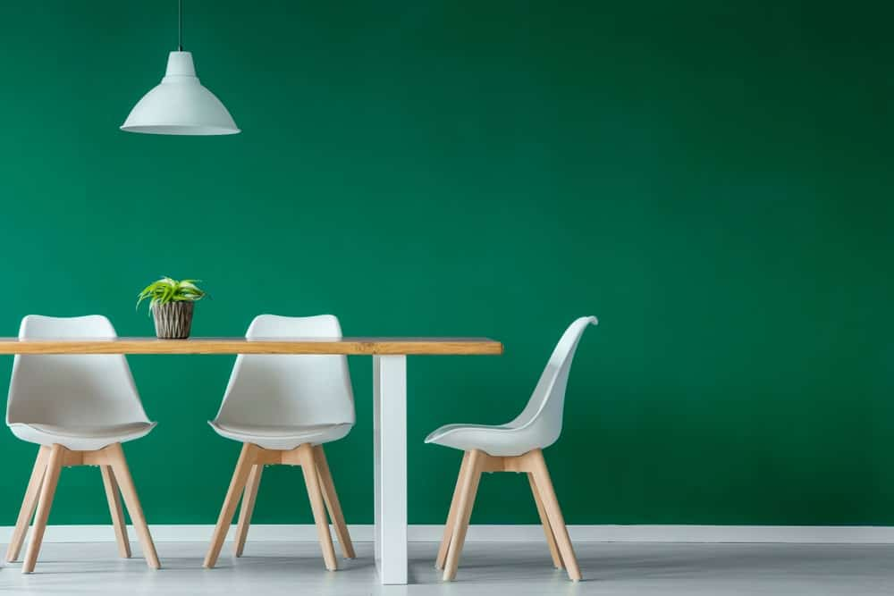 This is a lovely minimalist dining room with solid green walls contrasted by the white modern chairs and the white modern pendant light over the wooden table.