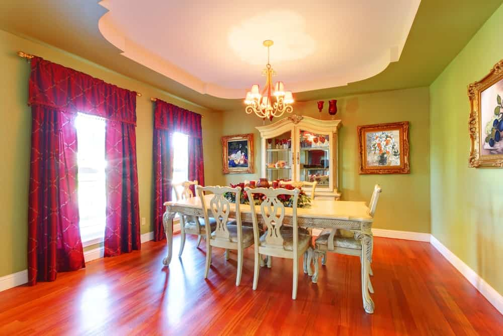 The elegant white tray ceiling is a nice capstone for the green walls that are accented with elegantly framed artworks that match the white dining table and its chairs.
