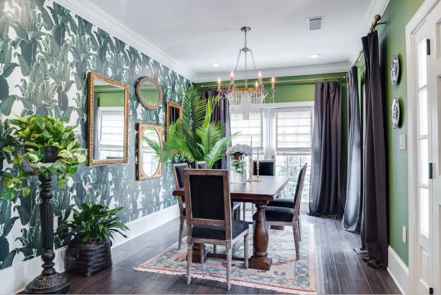 This narrow hallway-like dining room has green walls paired with another wall covered with leafy wallpaper and a white ceiling that complements the tall window by the head of the wooden table.