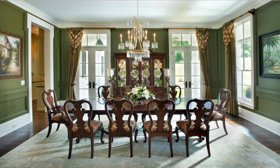 This is an elegant traditional dining room that has a wooden dining table paired with wooden chairs that contrast the green walls that have French glass doors and windows matching the white ceiling.