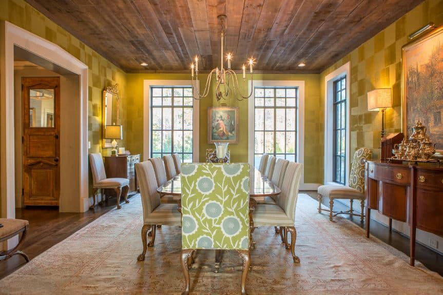 The yellow-green walls have a subtle checkered pattern that works well with the floral patterns on the cushioned chairs surrounding the long wooden dining table topped with a thin brass chandelier.