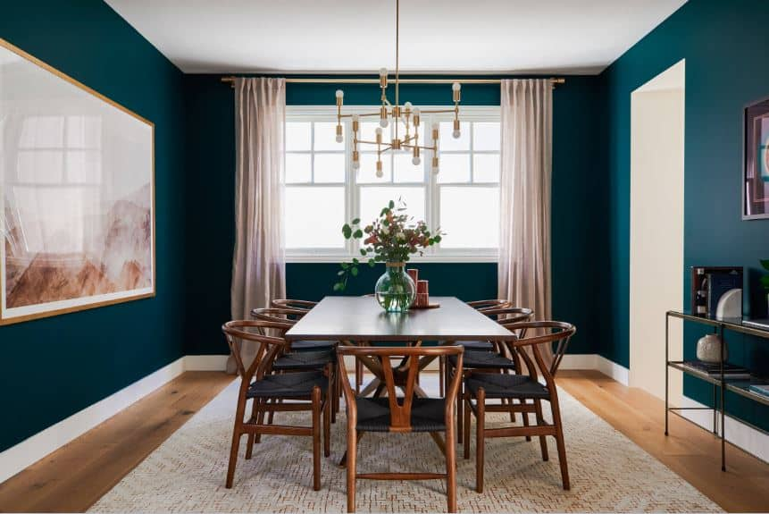 The wooden dining table is surrounded by wooden wishbone chairs that have green woven wicker seats that match the dark green walls adorned with a large artwork mounted beside the table.