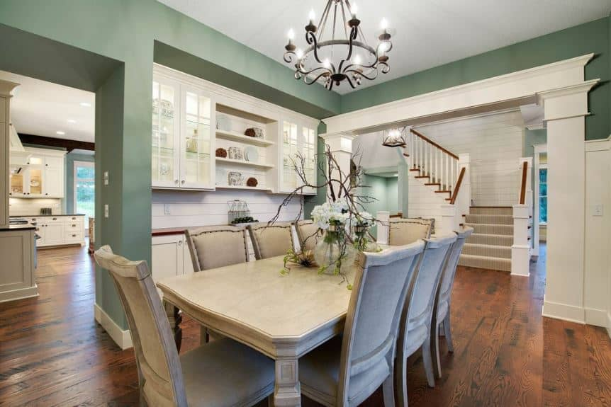 The white ceiling, white doorway and built-in cabinets are a good match for the green walls of this simple dining room. The dark iron chandelier brings an elegant contrast for the beige dining set.