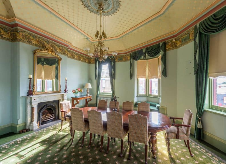An elegant and intricate cove ceiling of beige patterns and a golden chandelier is a good background for the green-carpeted flooring and light green walls that have a fireplace inlaid with green stone at the head of the wooden dining table.