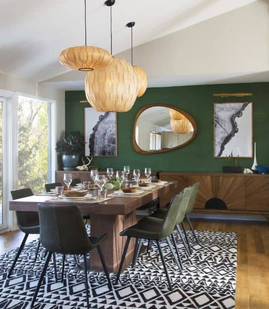The green walls of this dining room is a nice background for the peculiar artworks and pendant lights over the wooden table surrounded by matching green chairs.