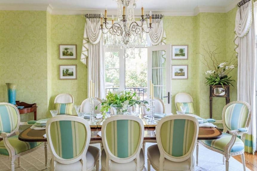 The white curtains of the windows and glass doors are a nice complement for the walls that are covered with green floral wallpaper. This is a nice pairing for the green and blue stripes of the oval-backed chairs around the dining table.