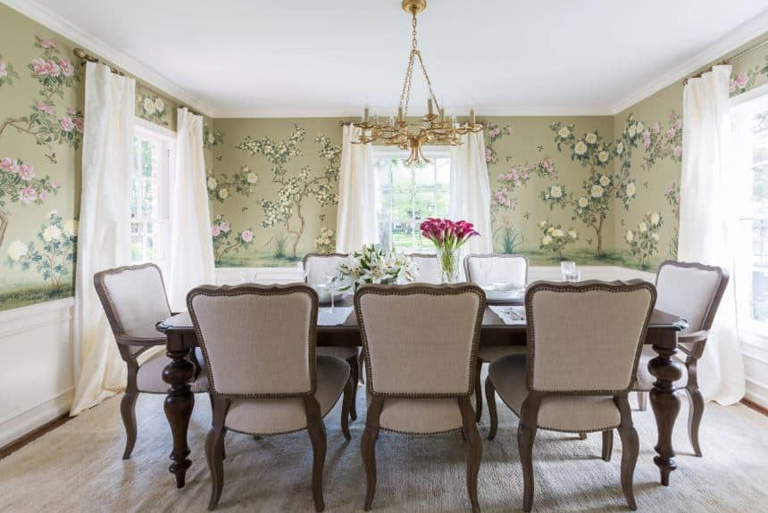 This is a chic dining room with floral designs on the avocado walls that bear a trio of curtained windows that illuminate the elegant wooden table.