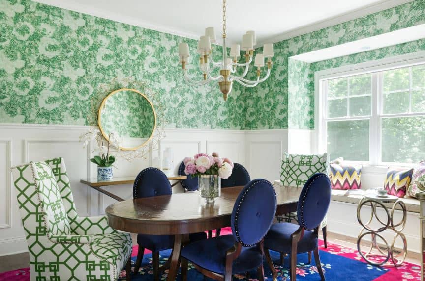 The chic green floral walls have white wainscoting that emphasizes the dark wood dining table and blue oval-back cushioned chairs.
