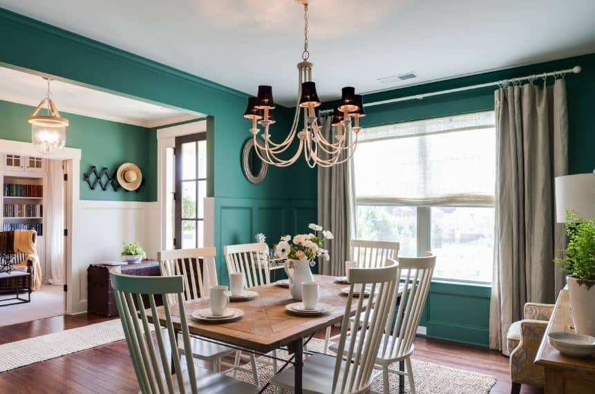 The white slat-backed dining chairs are a nice contrast for the wooden table that complements the green walls and hardwood flooring.