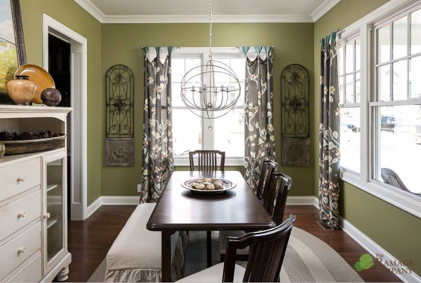The avocado walls have white molding that blends with the white ceiling that contrasts the dark wood elements of the table, chairs, and flooring.