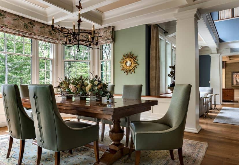 The dining chairs surrounding the elegant wooden table have leather cushions that match the green walls that contrast the white coffered ceiling with a dark iron chandelier.