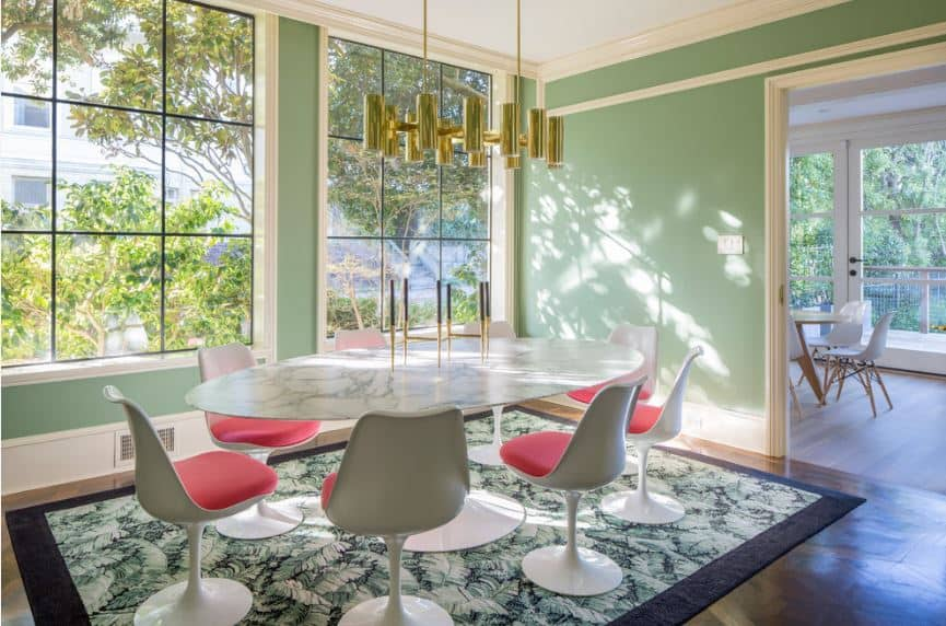 The modern white chairs with red cushions are a nice pairing for the modern marble top dining table that is illuminated by large windows on the green walls.