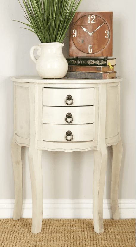 Small half-moon accent table with drawers.