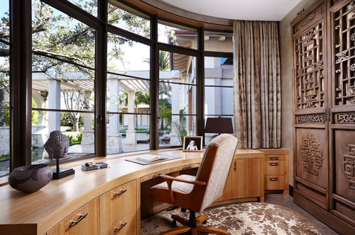 Asian home office with glass windows and carpeted floor.