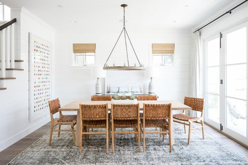 Beach dining room with white walls and stylish rug.