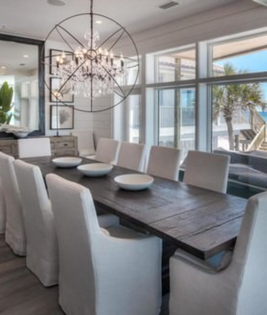 Beach dining room with unique chandelier and glass windows and door.