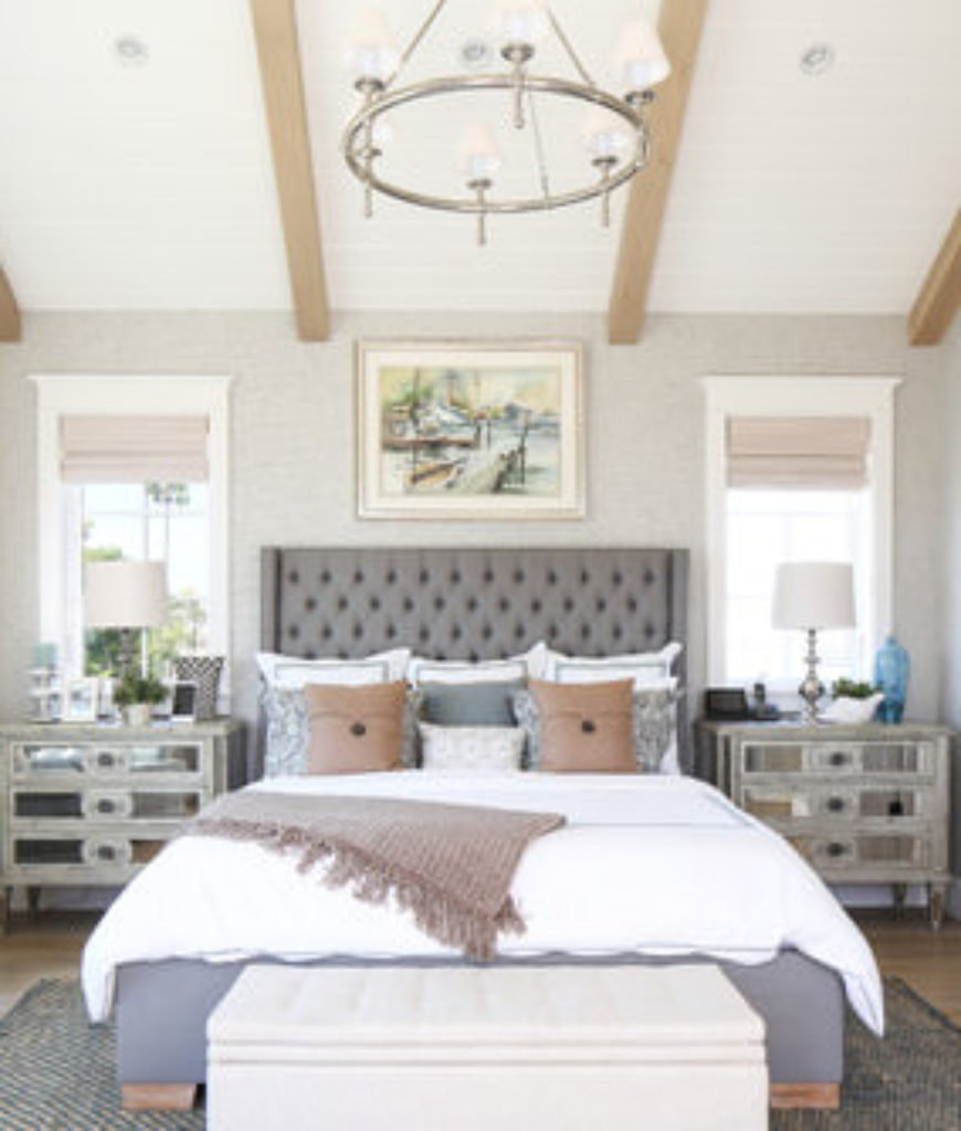 Coastal mid-sized bedroom in grayish palette with vaulted ceiling, wood beams, elegant furniture and wood flooring.