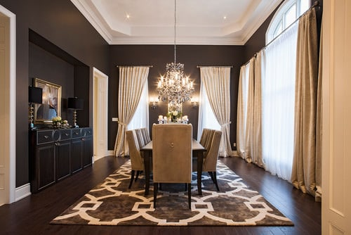 Attractive Black Transitional Dining Room With Chandelier, White Ceiling, And Floor  With Rug.