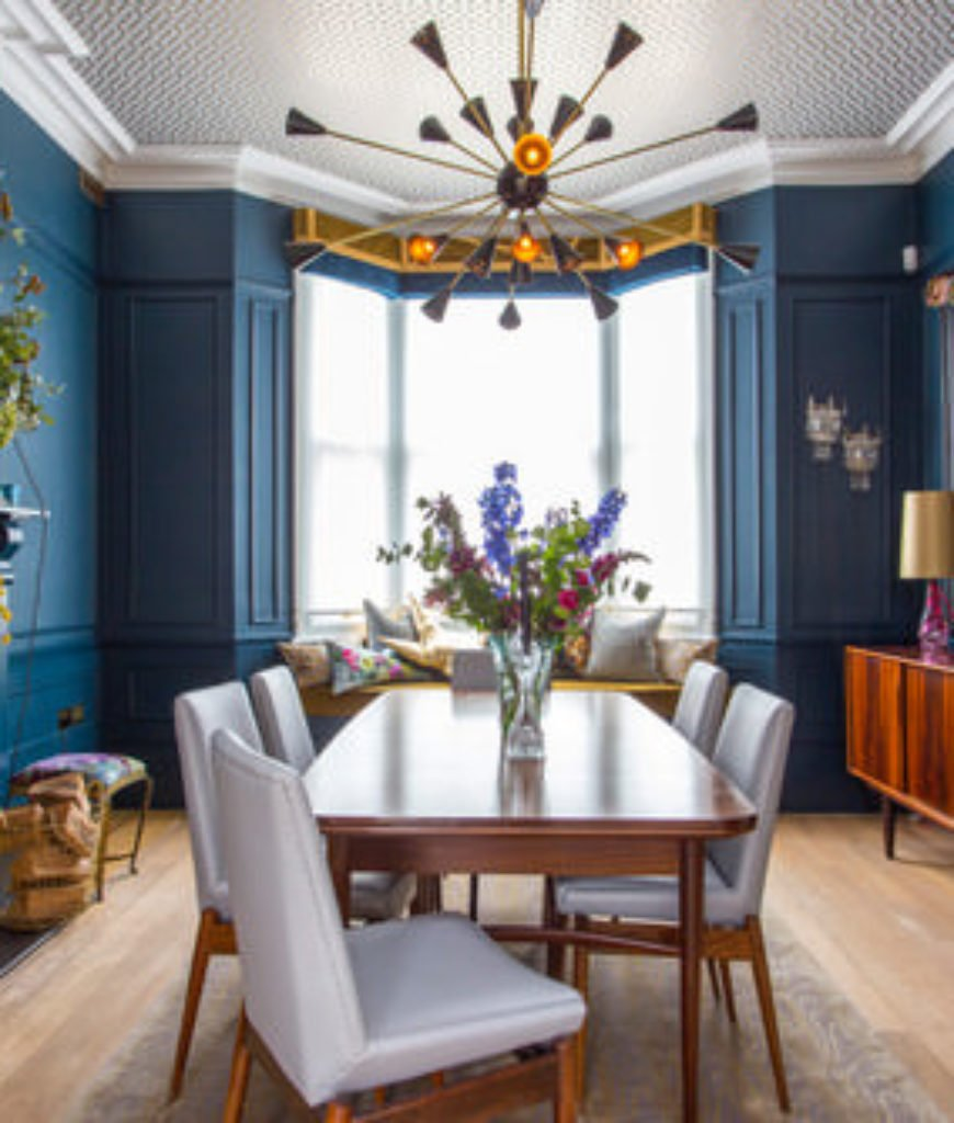 Eclectic blue dining room with chandelier and hardwood floor.