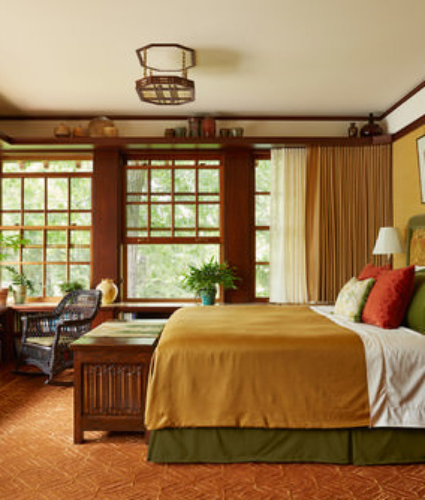 Lots of colors are happening in this craftsman master bedroom that features a patterned wood flooring and multiple hung window with wood frames.