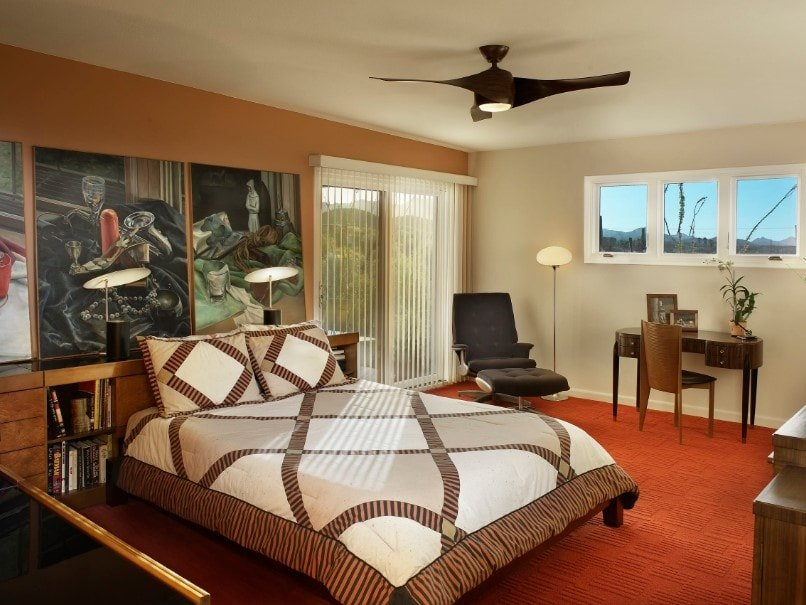 This primary bedroom boasts artistic wall decor on the room's orange wall. It features a modish bed setup lighted by stylish table lamps.