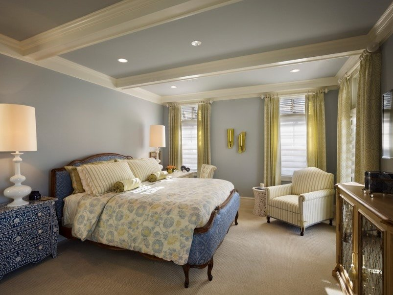 Eclectic primary bedroom boasting a large elegant bed setup lighted by large classy table lamps on both sides. The room features blueish gray walls and ceiling, along with carpeted flooring.