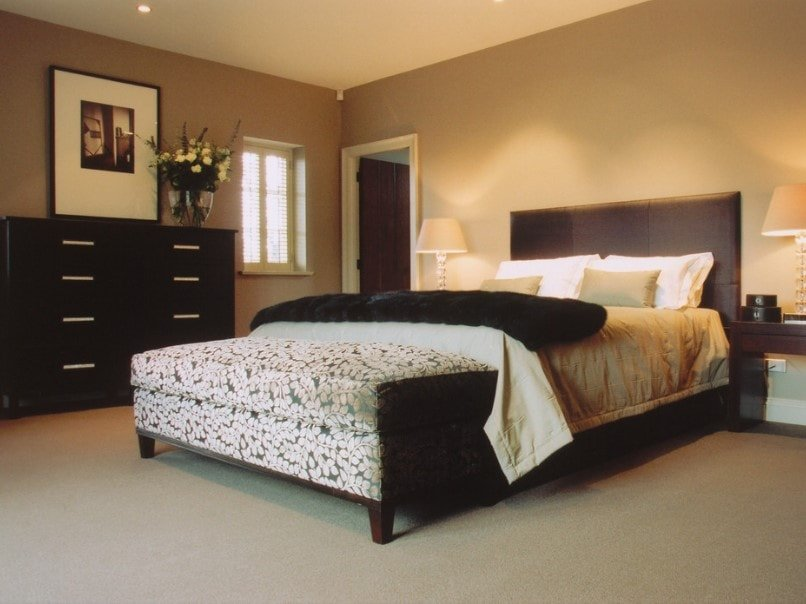 A focused shot at this primary bedroom's classy bed lighted by table lamps on both sides, surrounded by brown walls and carpeted flooring.