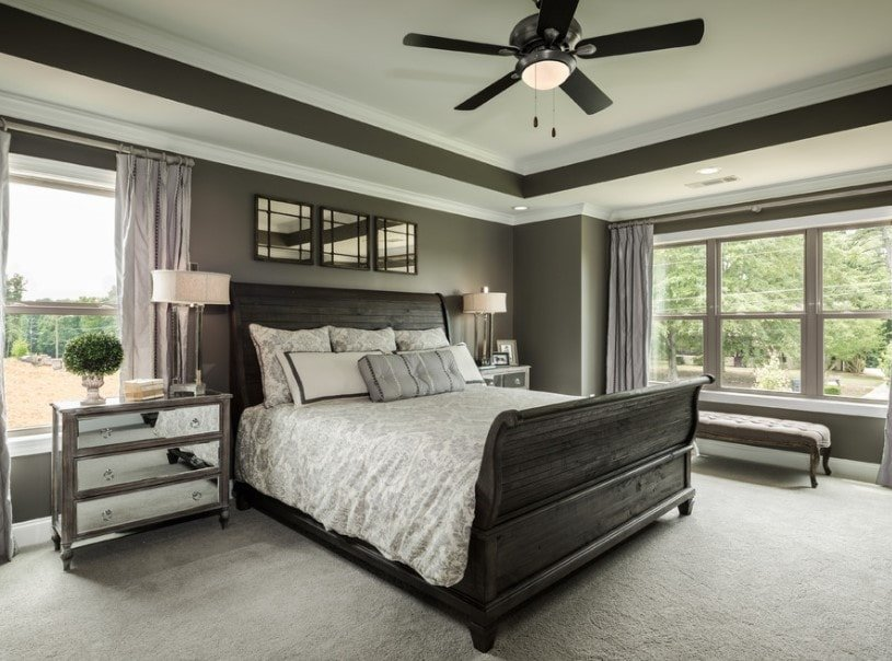 A focused shot at this primary bedroom's classy bed setup lighted by table lamps on both sides, surrounded by black walls and glass windows.