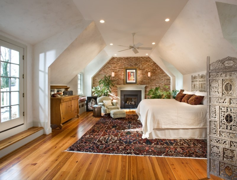 Large master bedroom featuring a shed ceiling and hardwood flooring. The room has a large comfy bed and a fireplace. The room also features a large area rug where the bed is set.