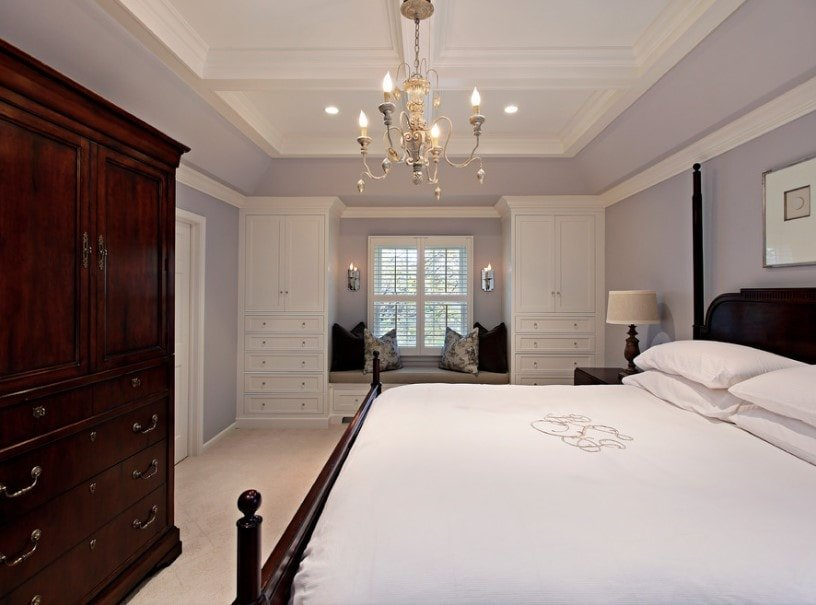 Master bedroom featuring light gray walls and a stunning ceiling lighted by a charming chandelier. The room offers a massive comfy bed and a closet with drawers.