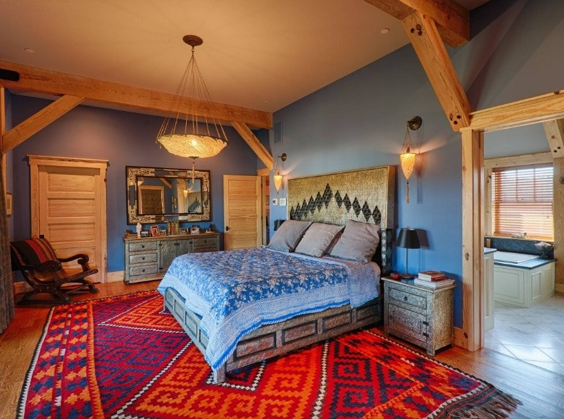 A spacious master bedroom with a large bed on top of a large stylish area rug covering the hardwood flooring. The room has blue walls and has its own bathroom.