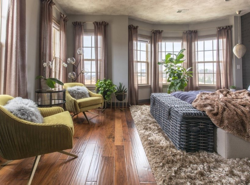Large Eclectic primary bedroom featuring gray walls, hardwood floors and a gorgeous ceiling. The room offers a cozy bed set on top of a large area rug.