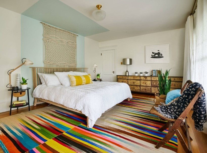 Eclectic master bedroom boasting a stylish and colorful area rug covering the hardwood flooring. The room has a large bed and a rustic side table.