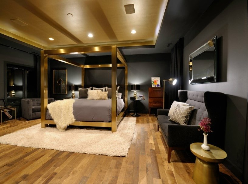 This Eclectic primary bedroom boasts a luxurious bed set surrounded by black walls. The room has a stunning tray ceiling and hardwood flooring.