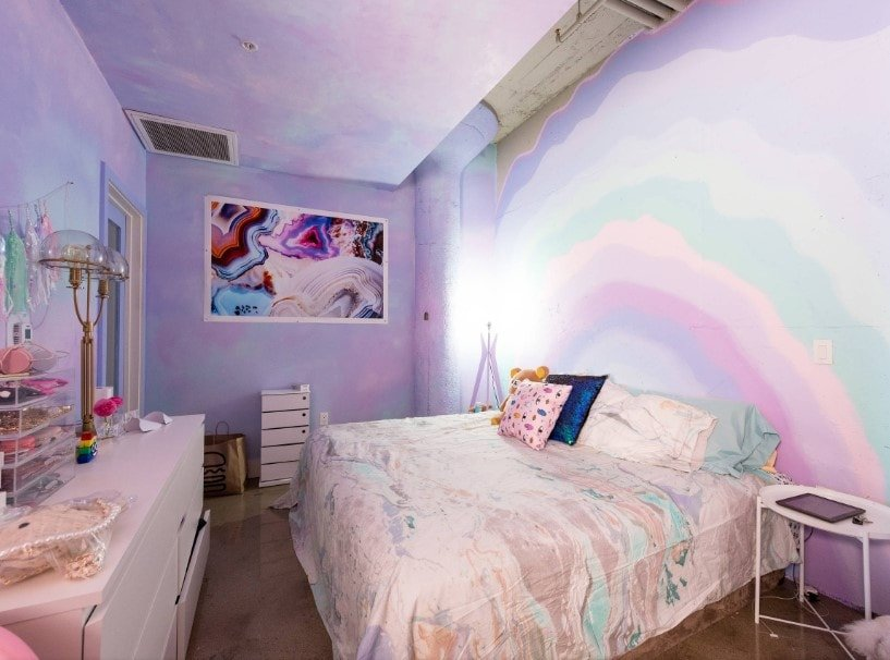 A girls' bedroom boasting purple walls with an abstract wall art decor. The room offers a large comfy bed and a white side table.