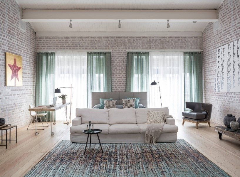 A spacious Eclectic primary bedroom featuring brick walls and a tall ceiling, along with hardwood flooring topped by an area rug. The room has a modern gray bed together with a study desk on the side.