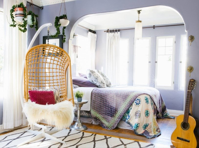 This Eclectic primary bedroom offers a cozy bed setup surrounded by purple walls. The room features hardwood floors topped by an area rug.