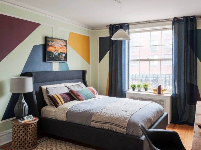 Primary bedroom offering a modern cozy bed surrounded by stylish walls and lighted by a pendant light.