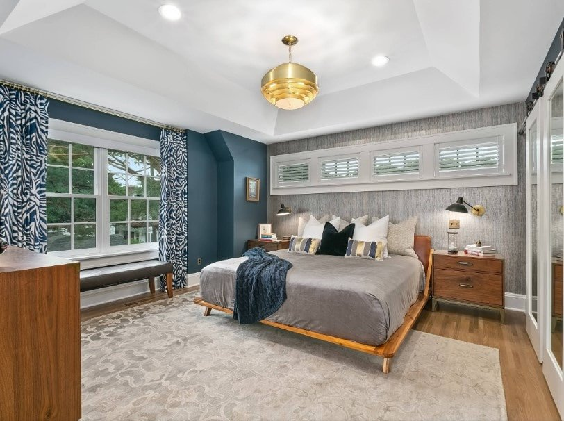 This primary bedroom offers stylish walls and hardwood floors topped by an area rug. The room offers a cozy bed set lighted by a gorgeous gold-finished pendant light.