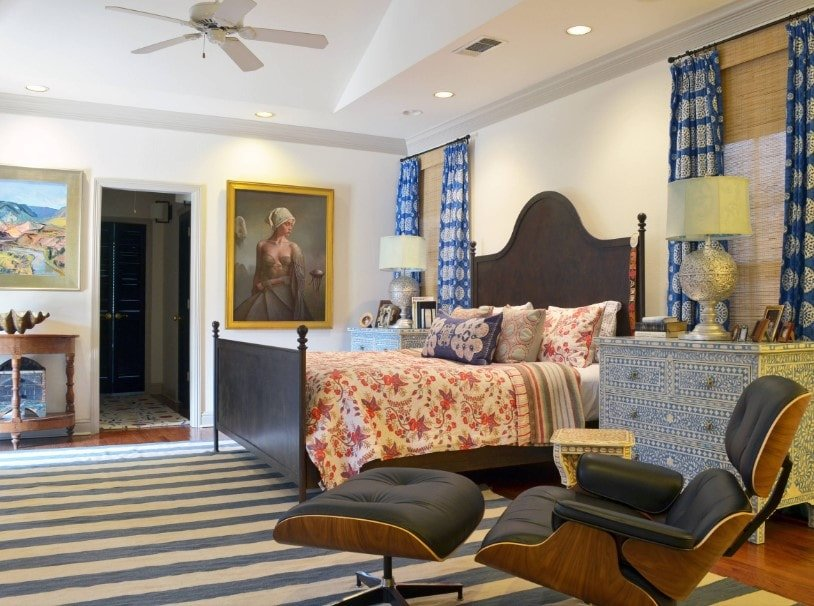 A spacious primary bedroom boasting an elegant bed lighted by table lamps on both sides, along with multiple artistic wall decors on the white walls.