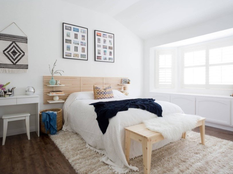 An Eclectic master bedroom featuring white walls and ceiling, along with hardwood flooring topped by a gorgeous area rug. The room offers a comfy bed with built-in shelving on both sides.