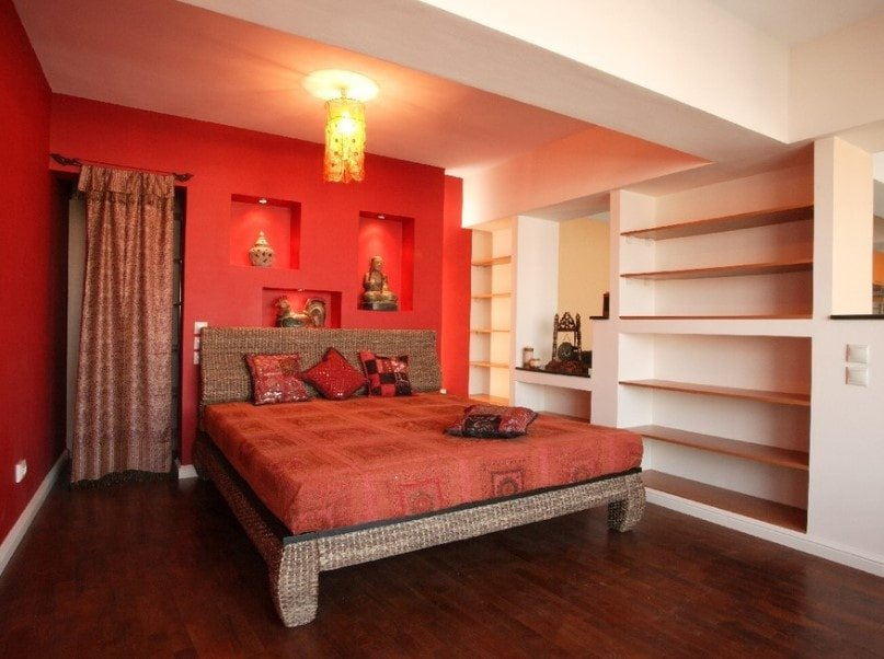This master bedroom offers a comfy bed surrounded by red and white walls and is lighted by a charming ceiling light. There are multiple built-in shelving along with a built-in desk in the room.