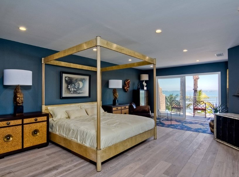 Primary bedroom boasting an elegant bed setup lighted by classy table lamps on both sides, surrounded by blue walls and hardwood floors.