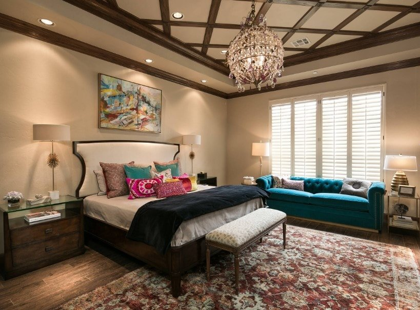 This primary bedroom boasts a glamorous chandelier hanging from the tray ceiling with magnificent design. The room offers a large cozy bed along with a blue elegant couch on the side.