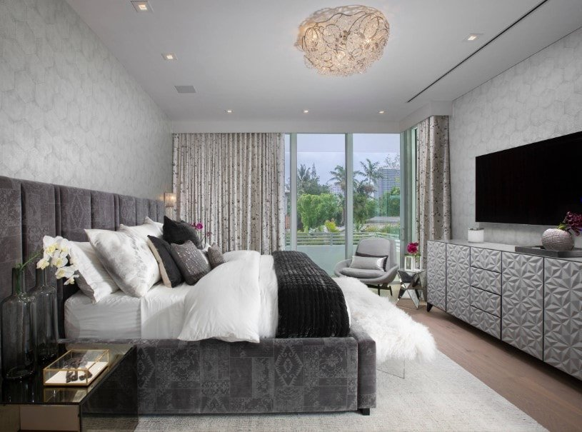 Primary bedroom with stylish walls and hardwood floors. The room boasts a luxurious gray bed set together with a large widescreen TV set in front of the bed.